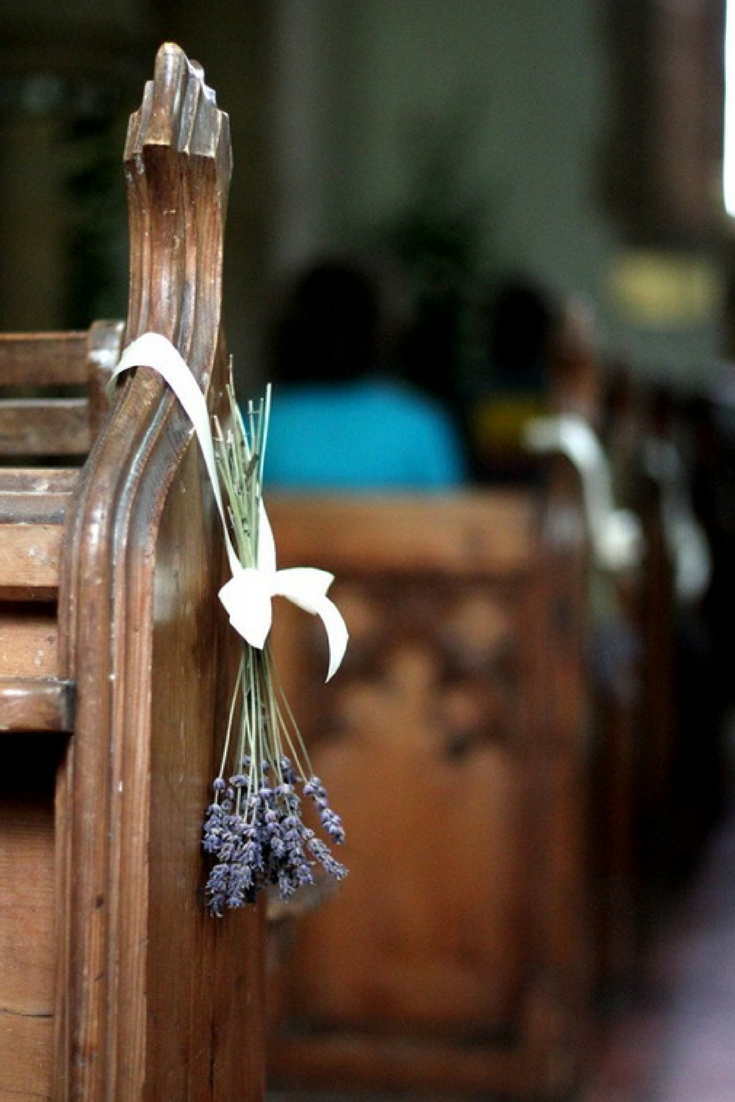 lavender bunches hanging from pew for wedding