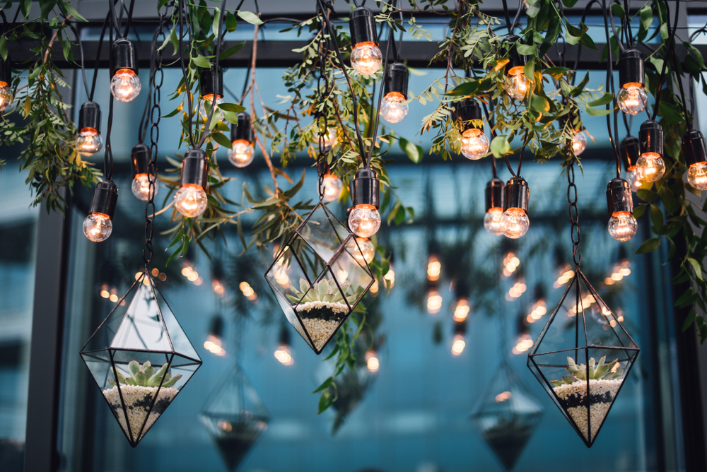 Hanging terrariums and white string lights at a wedding reception