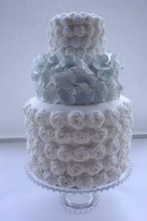 tiered wedding cake with roses and blue hydrangeas