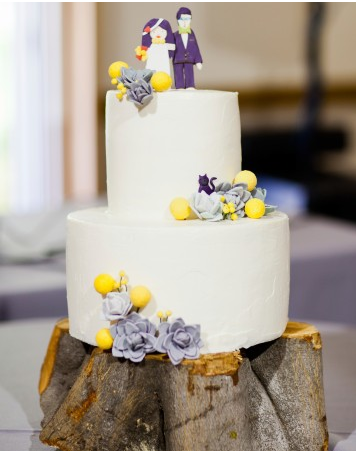 white tiered wedding cake with yellow and purple flowers