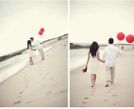 couple walking along beach with red balloons for engagement photo shoot
