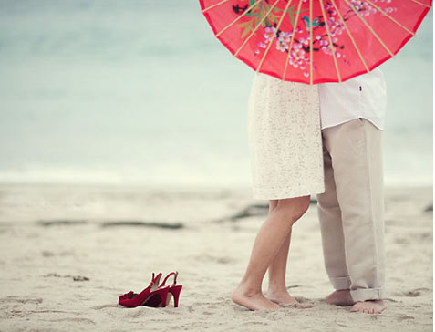 Couple holding red parasol for engagement photo shoot