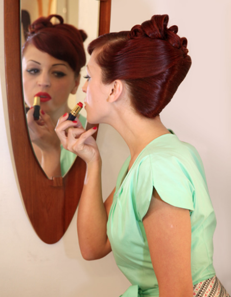 woman putting on lipstick in mirror