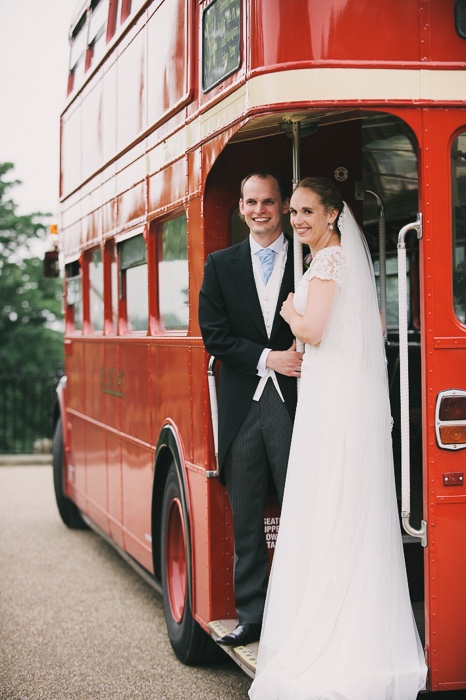 bride and groom on red London double decker bus